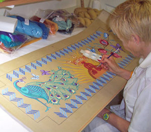 woman painting a needlework canvas